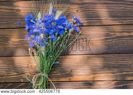 A Bouquet Of Cornflowers And Ears Of Wheat Or Rye On A Brown Wooden Background. Blooming, Flower Bou
