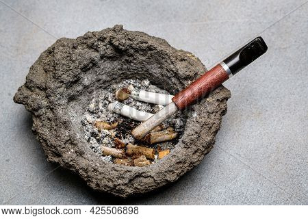 Cigarette Holder And Cigarette Butts In An Old Dirty Volcanic Lava Ashtray. Close-up. Selective Focu