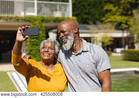 Senior african american couple spending time in sunny garden together taking selfies and smiling. retreat, retirement and happy senior lifestyle concept.