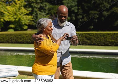 Senior african american couple spending time in sunny garden together using smartphone and smiling. retreat, retirement and happy senior lifestyle concept.