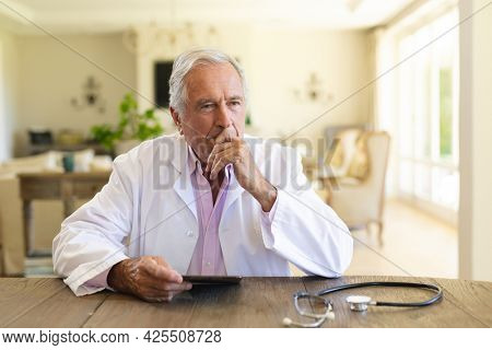 Senior caucasian male doctor sitting at table using tablet computer. medicine and healthcare services concept.