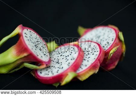 Slices Of Dragon Fruit Or Pitaya With Pink Skin And White Pulp With Seeds On Black Background. Exoti