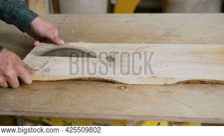 Saws Wood With A Modern Circular Saw In A Workshop. A Carpenter Is Sawing A Board On A Saw.