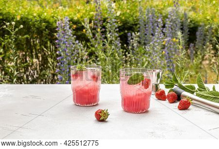 Cold, Strawberry Mojito Mocktail Or Cocktail With Mint, Ice Cubes In Front Of The Garden. A Deliciou