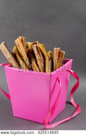 Beautiful Pink Gift Box With Pet Treats. Open Box Full Of Bully Sticks For Dogs On Gray Background.