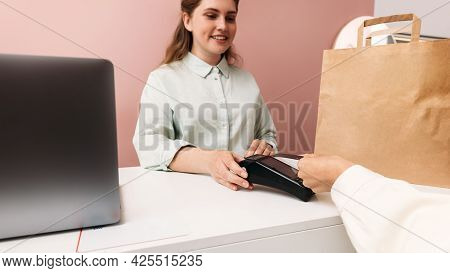 Smiling Boutique Owner Holding Pos Terminal While Customer Making Payment With Credit Card