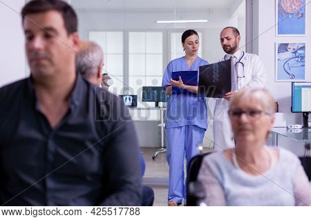 Specialist Doctor Holding Patient X-ray Explaining Disease Diagnosis To Nurse While Standing In Hosp
