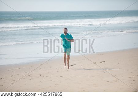 Morning Jogging On A Sandy Beach Near Sea Or Ocean. Man Running On Beach.