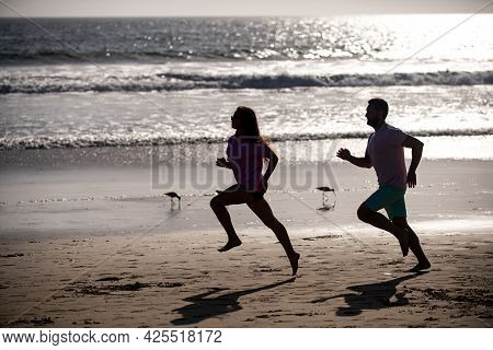 Couple Running On Beach. Silhouette Of Young Man And Woman Running Jogging Along The Sea.