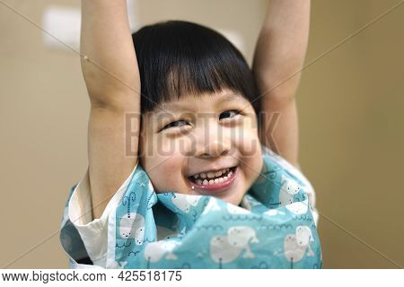 Child Hands Up With Smiling Face.  Portrait Of Lively Boy Arm Raised With Smiling Face And Eating Me
