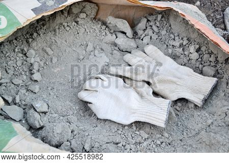 White Dirty And Used Cotton Gloves Of A Construction Worker Are Thrown Into An Open Paper Bag With C