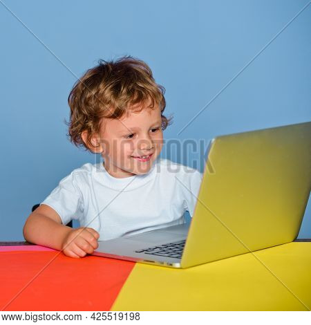 Little Boy Pupil With Happy Face Expression Near Laptop, School Concept. Kid With A Notebook. Closeu