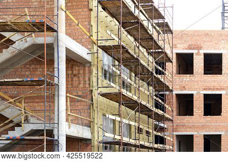 Thermal Insulation Of A Red Brick House With Mineral Wool. The Use Of Scaffolding When Building A Ho