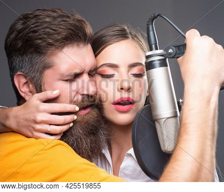 Singer Couple Singing Rock. Sound Producer Recording Song In A Music Studio. Sexy Man And Woman Sing