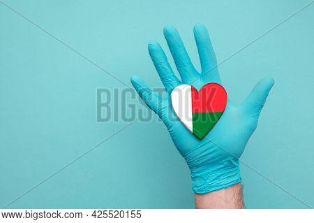 Madagascar Medical Health Heart. Nurse Hand Holding Country Heart Flag