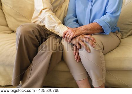Mid section of senior caucasian couple sitting on sofa holding hands. retreat, retirement and happy senior lifestyle concept.