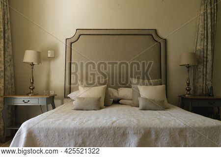 General view of luxury sunny bedroom with large bed and night tables. interior design and home decoration concept.