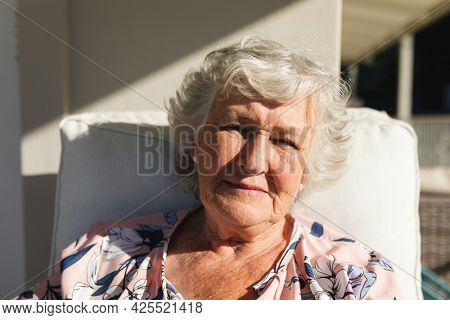 Portrait of senior caucasian woman sitting on balcony looking at camera. retreat, retirement and happy senior lifestyle concept.