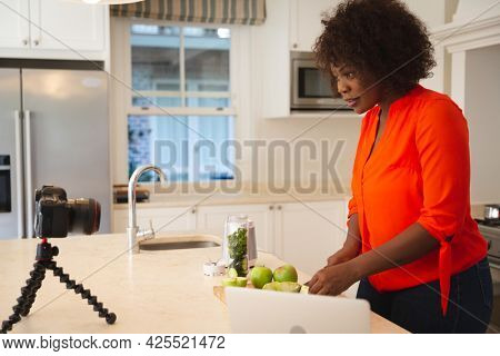 Happy african american woman in kitchen preparing health drink, making vlog using laptop and camera. online cookery vlogger at home.