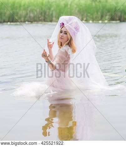 Beautiful Girl In Wreath Of Flowers At Lake. Portrait Of Young Beautiful Woman. Young Pagan Girl Con