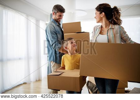 Happy Family With Children Moving With Boxes In A New Apartment House.