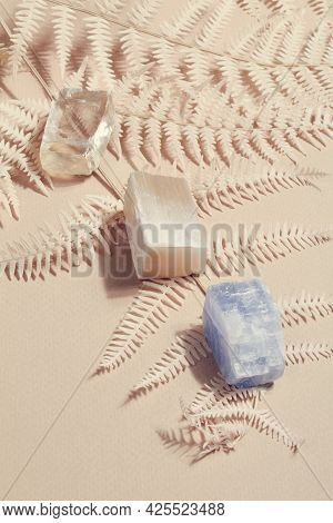 Many Crystal Minerals With Dry Fern On Beige Background. Magic Rock For Crystal Ritual, Witchcraft,