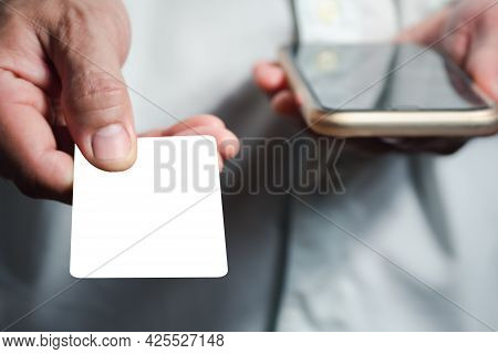 A Man's Hand Is Holding A White Card, Extending It Forward To Pay For The Goods. The Concept Is To U