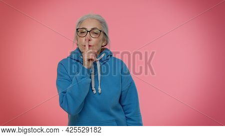 Shh Be Quiet Please. Elderly Gray-haired Granny Woman Presses Index Finger To Lips Makes Silence Ges