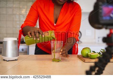 African american woman in kitchen pouring health drink, making vlog using laptop and camera. online cookery vlogger at home.