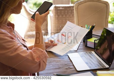 Midsection of caucasian woman working at home, using laptop and smartphone, holding paperwork. technology and communication, flexible working from home.