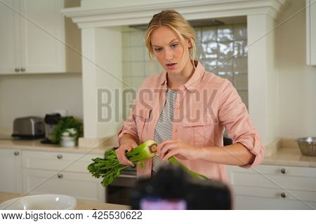 Caucasian woman in kitchen preparing food and using camera, making cooking vlog. technology and communication, cookery vlogger at home.