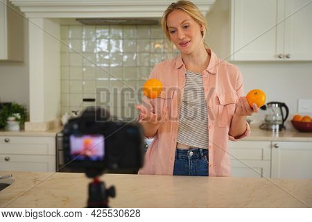 Smiling caucasian woman in kitchen holding oranges and using camera, making cooking vlog. technology and communication, cookery vlogger at home.