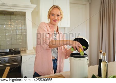 Portrait of smiling caucasian woman standing in kitchen preparing food, composting vegetable waste. spending free time at home.