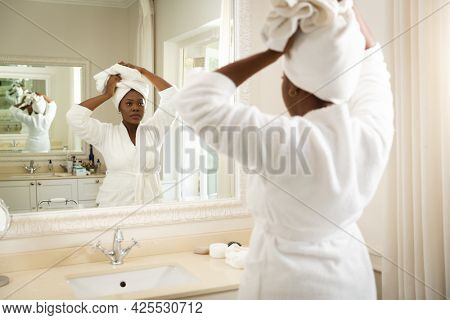 African american woman in bathroom wearing bathrobe, looking in mirror and putting towel on head. health, beauty and wellbeing, spending quality time at home.