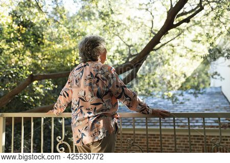 Senior caucasian woman standing on balcony and looking away. retreat, retirement and happy senior lifestyle concept.