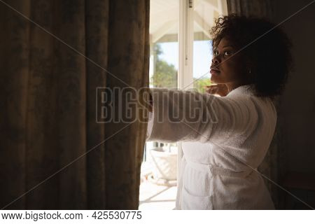 African american woman standing at sunny window drawing curtains and looking away. spending free time at home.