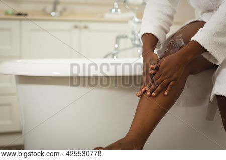 Midsection of african american woman sitting in bathroom wearing bathrobe, moisturising legs. health, beauty and wellbeing, spending quality time at home.