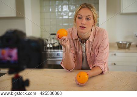 Caucasian woman in kitchen holding oranges and talking to camera, making cooking vlog. technology and communication, cookery vlogger at home.