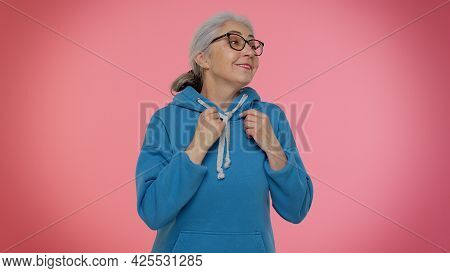 Ambitious Satisfied Egoistic Mature Old Granny Woman In Casual Blue Hoodie Winner Of Lottery Posing