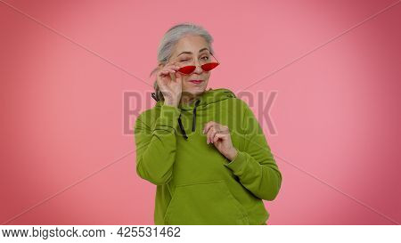 Happy Playful Elderly Stylish Granny Woman In Sunglasses Blinking Eye, Looking At Camera With Toothy