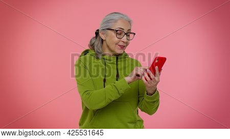 Cheerful Senior Old Granny Woman In Hoodie Using Mobile Phone Typing New Post On Web, Sms Message, B