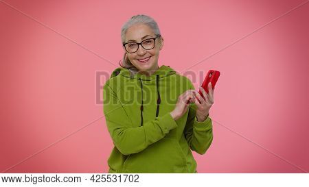 Happy Excited Joyful Elderly Granny Gray-haired Woman Use Mobile Cell Phone Typing Browsing Say Wow