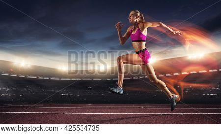 One Professional Female Runner, Jogger Training At Stadium In Evening. Caucasian Fit Athlete Practic
