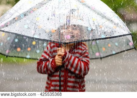 Little Toddler Girl Playing With Big Umbrella On Rainy Day. Happy Positive Child Running Through Rai