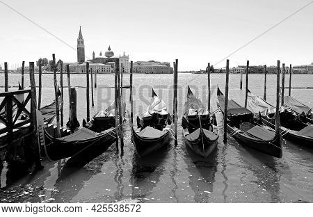 Moored Gondolas The Typical Boats In Venice With Black And White Effect And The Church Of Saint Geor