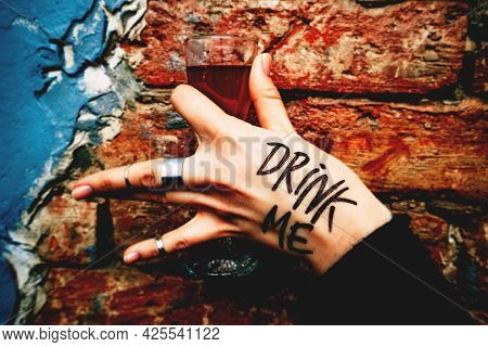 Alcoholic Drinks. Woman's Arm Holds Shot With Red Liqueur Drink Me