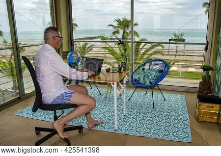 Man Tele Working From Home Dressed With A Elegant Shirt For Videoconference And Shorts And Bared Fee
