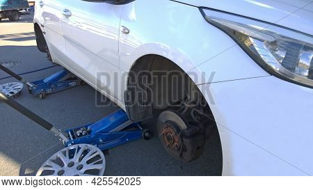 Car Raised On Jack. Changing Flat Tire On Your Own. Wheel Replacement. Outdoor Auto Repair Shop. Ser
