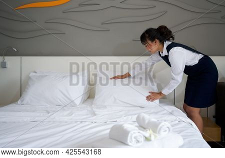 Young Hotel Maid Making The Bed. Hotel Staff In Blue Uniform Preparing Room For Guest.