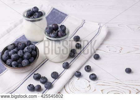 Greek Yogurt In A Glass Jar And Fresh Blueberries On A Rustic White Table. Healthy Food Concept. Sel